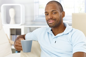 Happy man having tea at home
