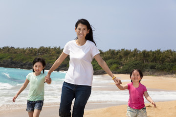 asian mother with children walking on the beach