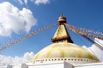 stupa with buddha eyes and prayer flags on clear blue sky backgr