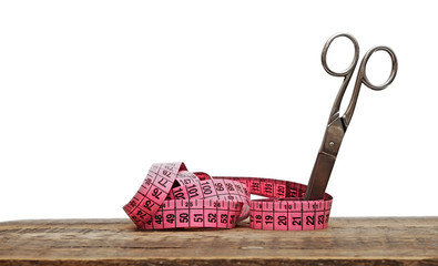 Old scissors and measuring tape on wooden background