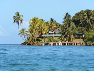 Tropical island with coconut trees and a dock leading to a small village, Central America, Archipelago of Bocas del Toro, Panama