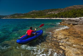 Man rowing in inflatable kayak at Adriatic sea. Hvar, Croatia