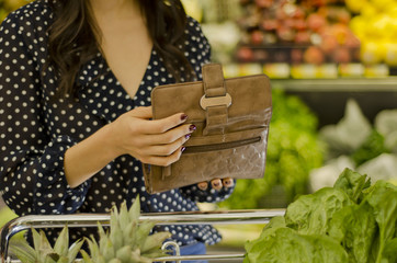 Young woman reaching at her wallet at the grocery store