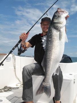 pêcheur heureux tenant un gros bar