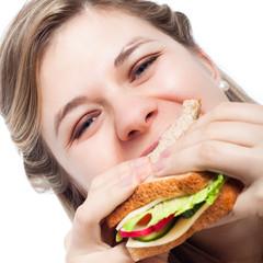 Happy woman eating sandwich