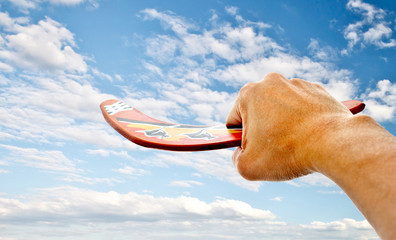 hand holdiing boomerang with blue sky