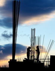 Silhouette of workers and unfinished building