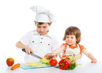 Two smiling kids mixing salad