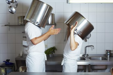 Two chefs having discussion with large pans on their heads