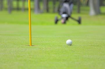 Golfball neben Fahne mit trolley im Hintergrund