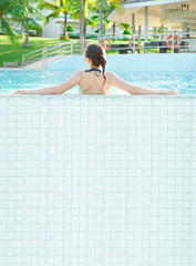 Woman sunbathing by the pool. Photo from behind