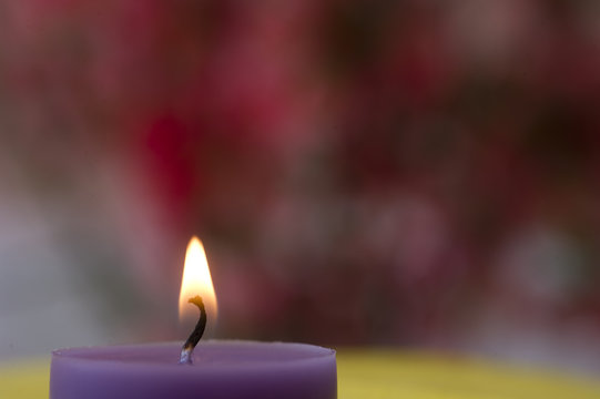 A purple candle in front of pink backround