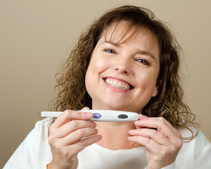 Happy middle-aged woman holding a positive pregnancy test