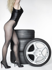 Sexy woman with High Heels and a set of summer tyres