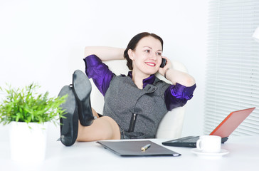 Business woman talk on telephone with legs on the table