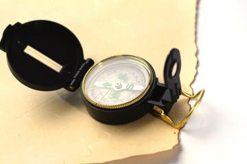 a compass on vintage paper, closeup