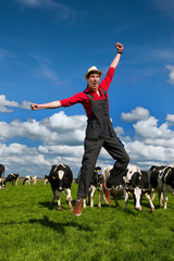 Happy farmer in field with cows
