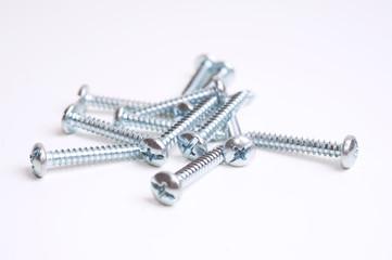 Heap of screws closeup on white background