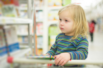 Adorable baby hold book near book stand in supermarket