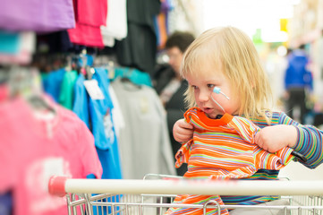 Adorable baby on cart choose clothes in supermarket