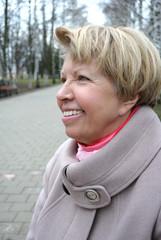 Smiling senior woman walking in the park