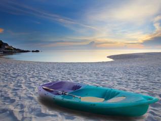 green sea kayak on sand beach