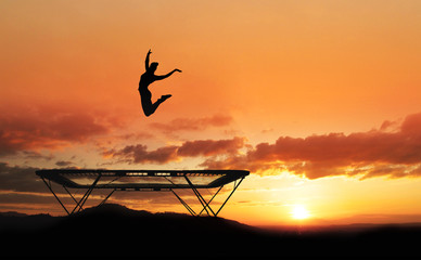 Wall Mural - silhouette of female gymnast on trampoline in sunset