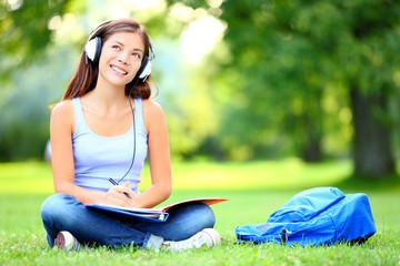 Leinwandbilder - Student listening music in park