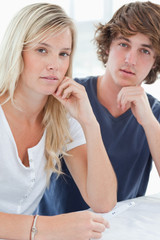 A worried couple with a pregnancy test looking at the camera