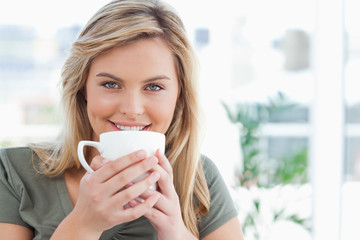 Woman looking forward, smiling with a mug up to near her mouth