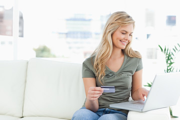 Woman smiles as she uses her laptop and credit card while sittin