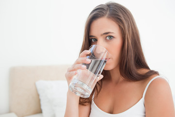 Woman looking forward drinking from a glass of water