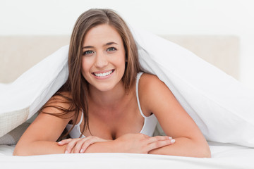 Woman lying at the end of the bed, smiling as she looks forward
