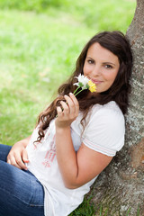 Young smiling woman smelling flowers while sitting against a tre