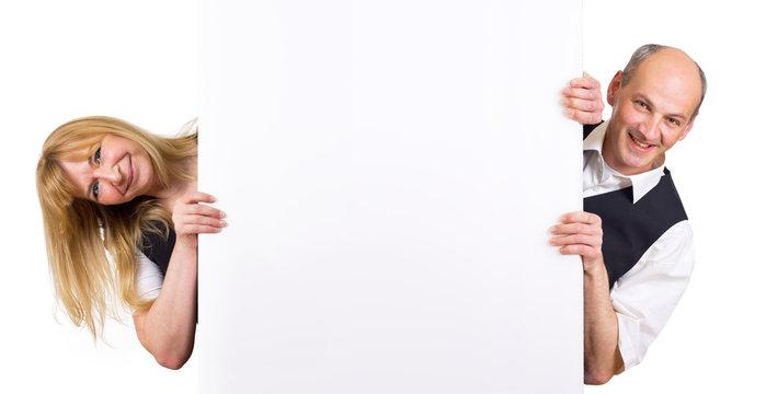 Mann und Frau schauen hinter Werbetafel hervor