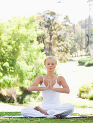 Woman sitting on the lawn in a yoga position