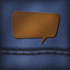 Blank leather jeans label in speech bubble shape on a blue jeans