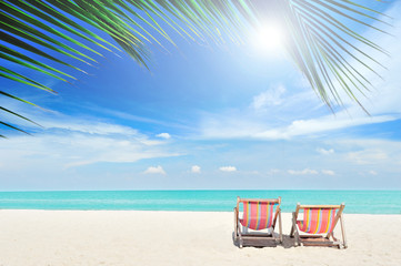 Beach chairs with palm leaves and cloudy blue sky