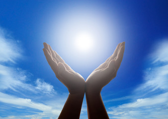 Hand holding the sun with cloudy blue sky in background