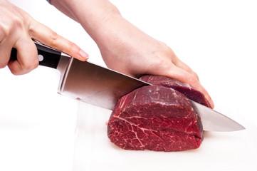 Zwei Hände schneiden ein Stück Rindfleisch