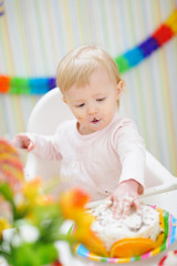 Eat smeared baby touching birthday cake