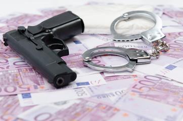 Pistole mit Geld und Handschellen