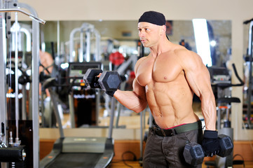 Bodybuilder shakes his biceps with dumbbell