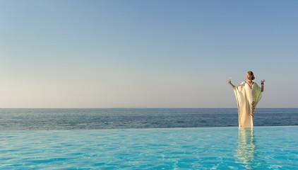 Woman in long dress like greek goddess posing near edge of infin