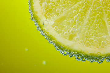 slice of lemon in the water with bubbles