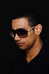 Latino male model with sunglasses on black background