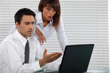 Shocked business couple in front of laptop