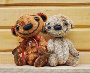 Teddy bears against a wooden wall
