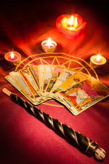 Tarot cards with a magic wand illuminated by candlelight.