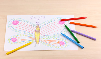 Children's drawing of butterfly and pencils on wooden background
